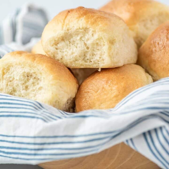 Bowl of fluffy baked dinner rolls .