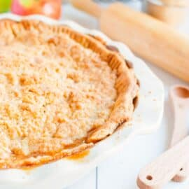 Dutch Apple Pie with streusel topping in a white pie plate.