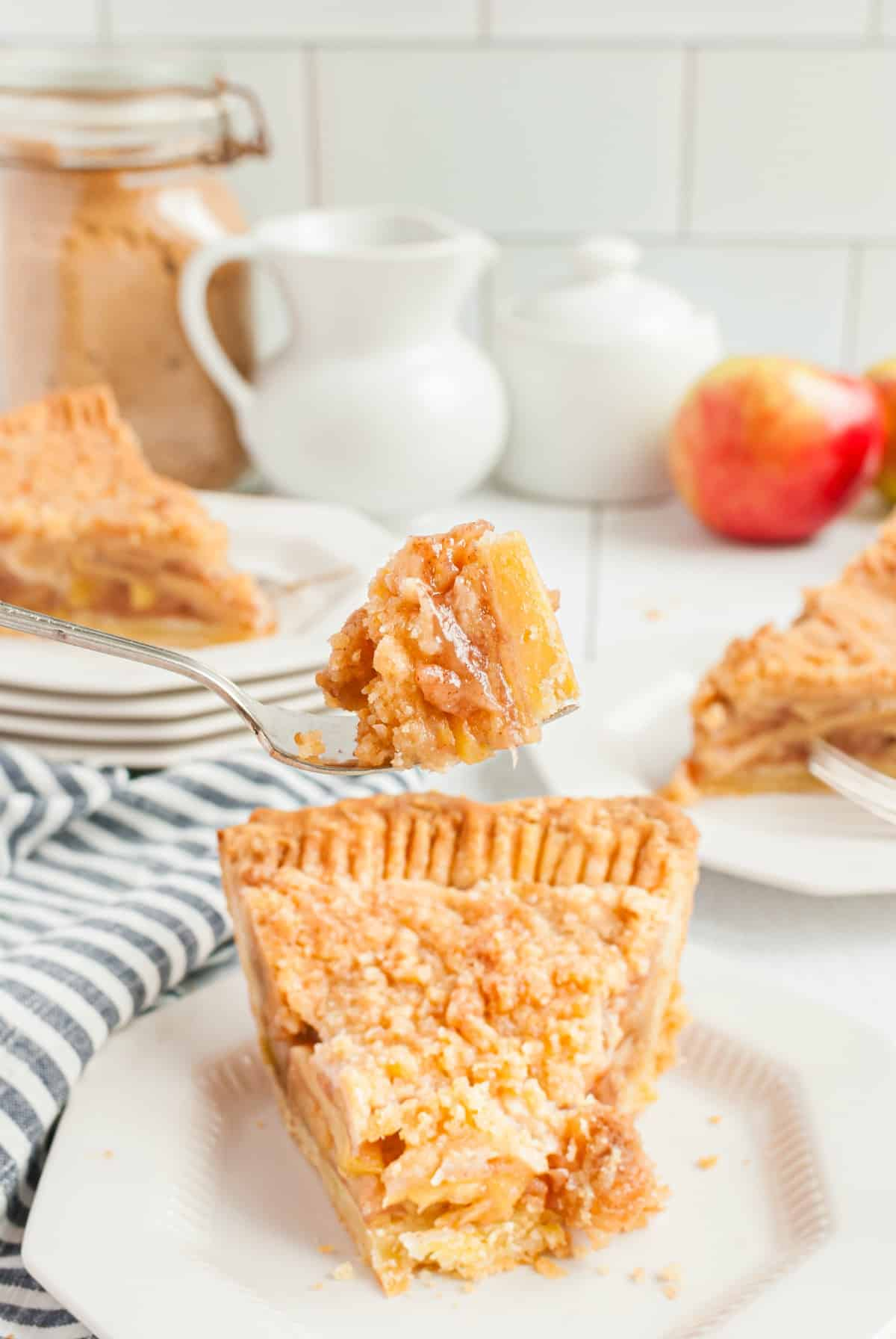 Slice of dutch apple pie on a plate with one forkful of pie being lifted.