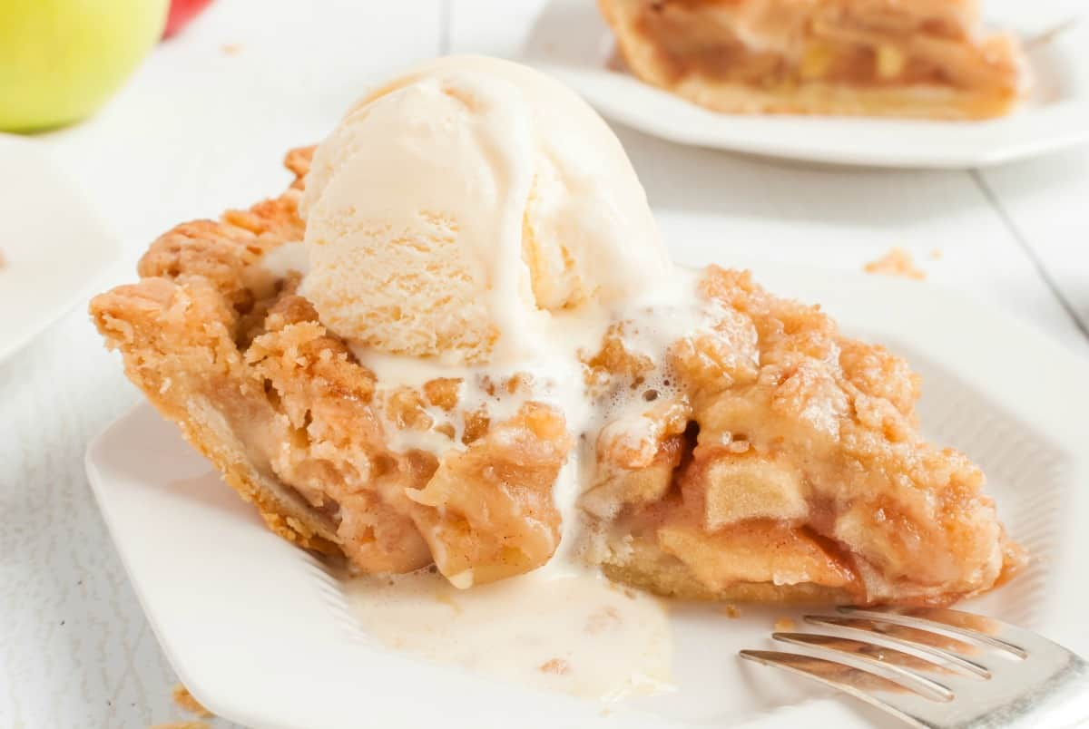 Slice of apple pie on a white dessert plate with a melting scoop of vanilla ice cream on top.