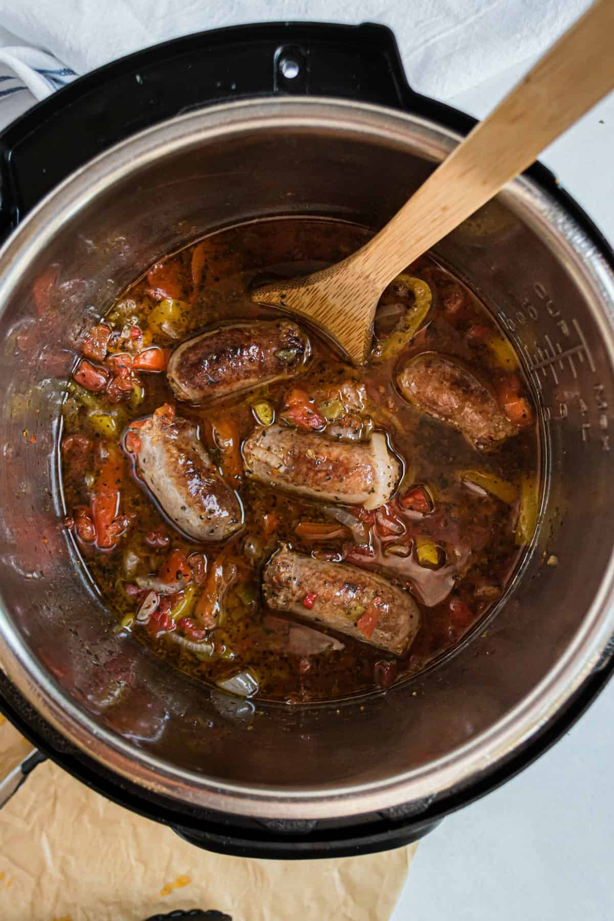 Instant Pot filled with italian sausage, peppers, and rotel tomatoes.