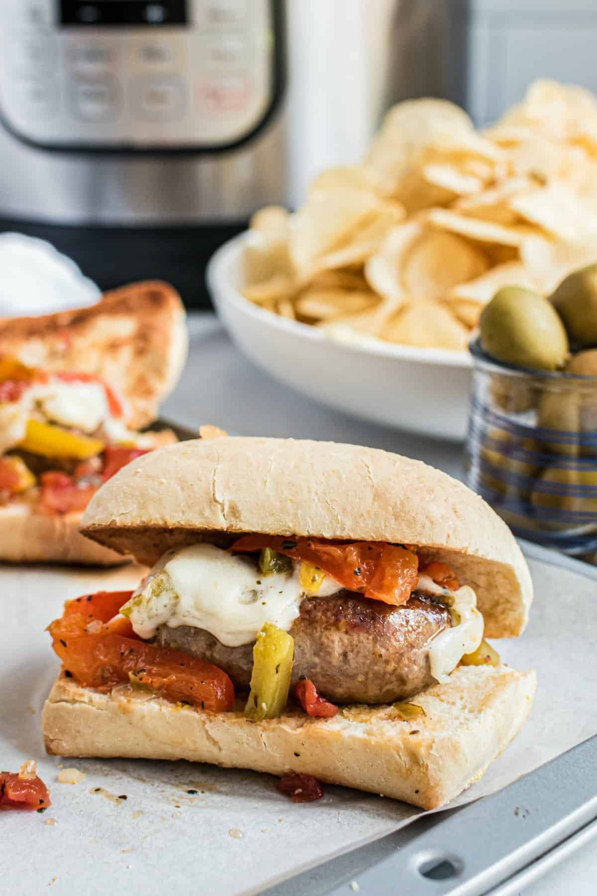 Sausage and peppers on a french roll with chips, olives, and pressure cooker in background.