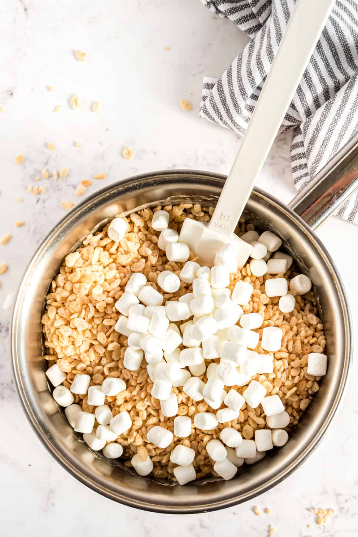 Melted butter and marshmallow for rice krispie treats in a sauce pan with cereal and more marshmallows being added.