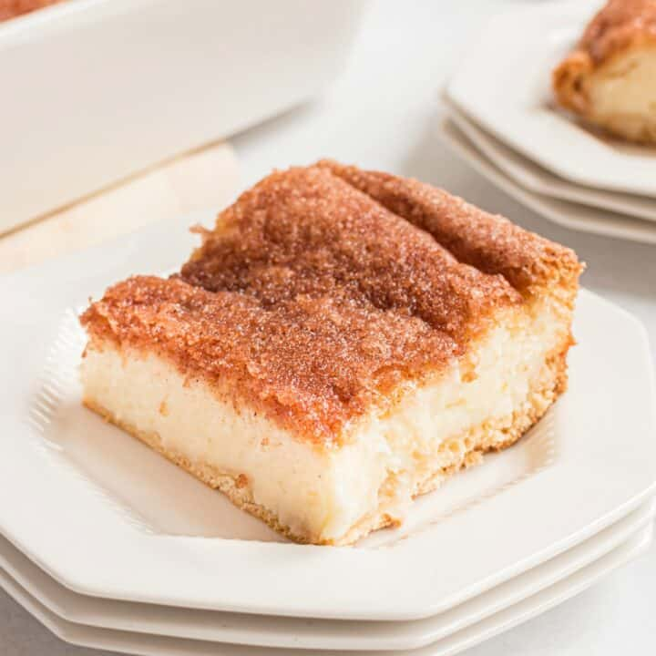 Slice of sopapilla cheesecake on a white plate topped with cinnamon sugar.