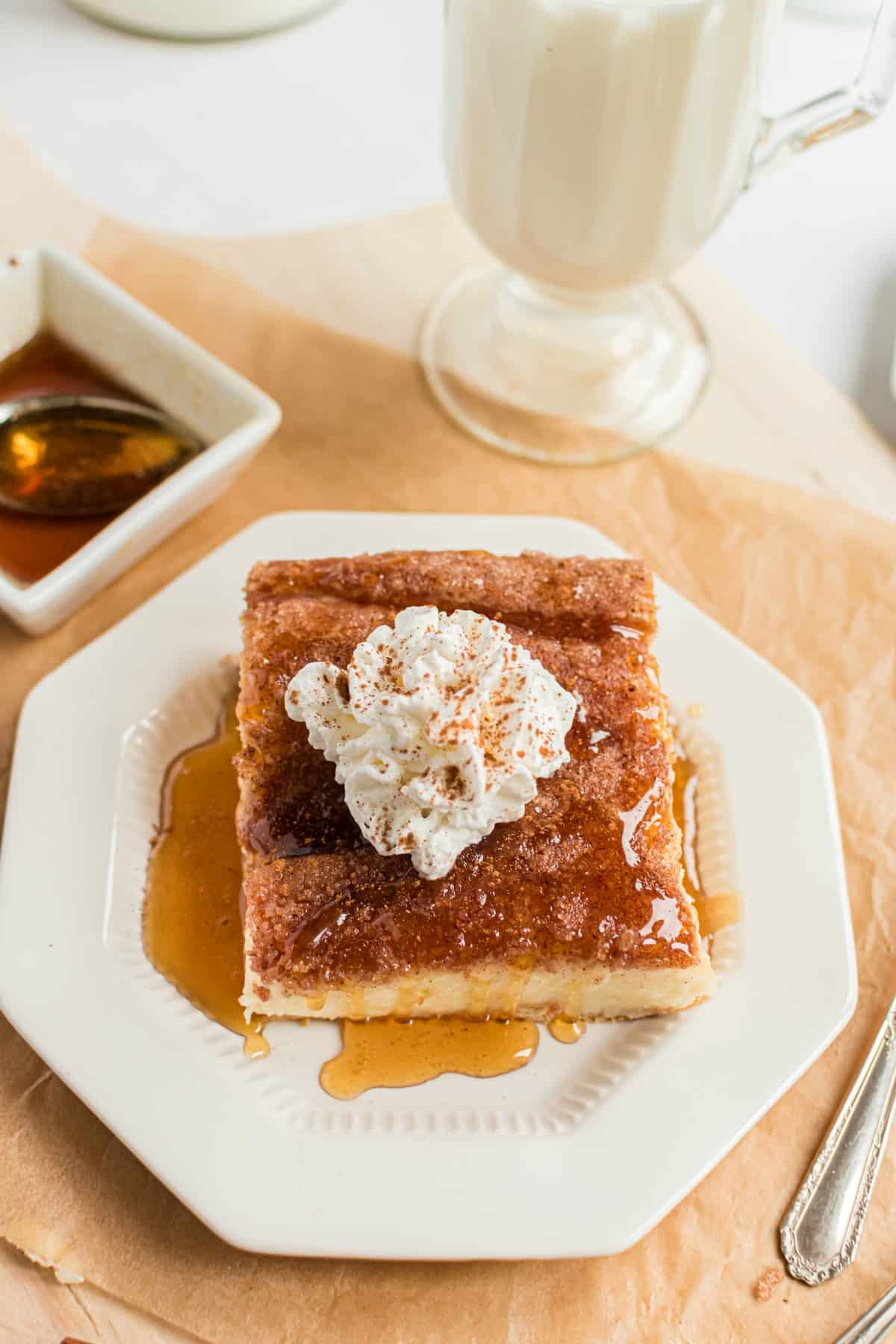 Slice of sopapilla cheesecake bar on a white plate, drizzled with honey and a dollop of whipped cream on top.