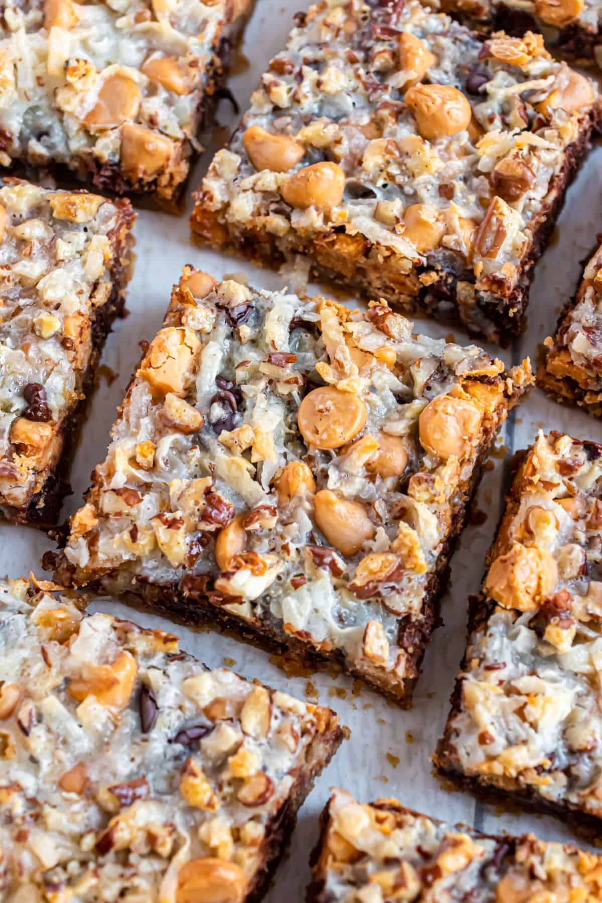 Gooey 7 layer bars on a parchment paper lined cookie sheet.