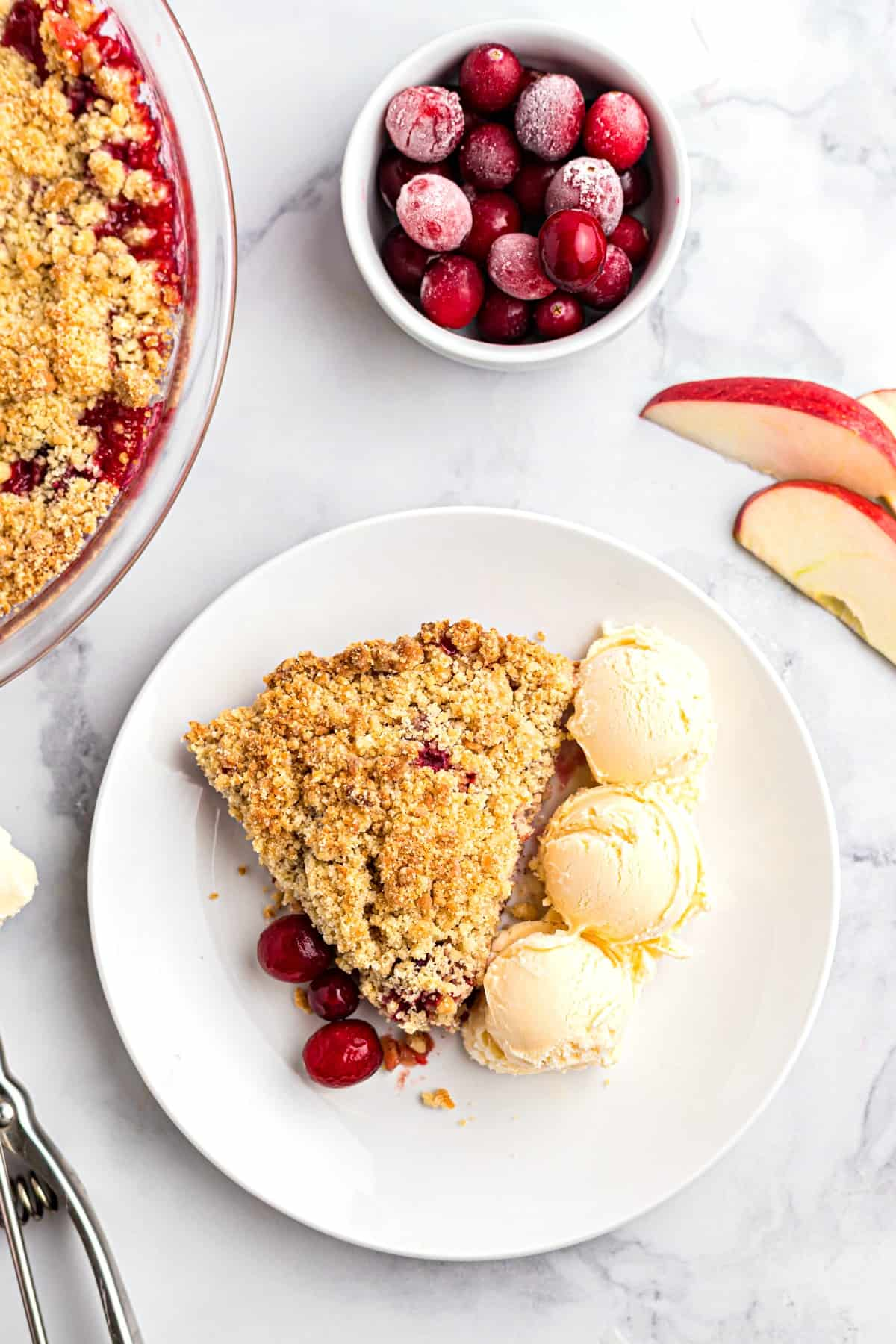 Three scoops of vanilla ice cream on a plate with a slice of apple cranberry crumble.