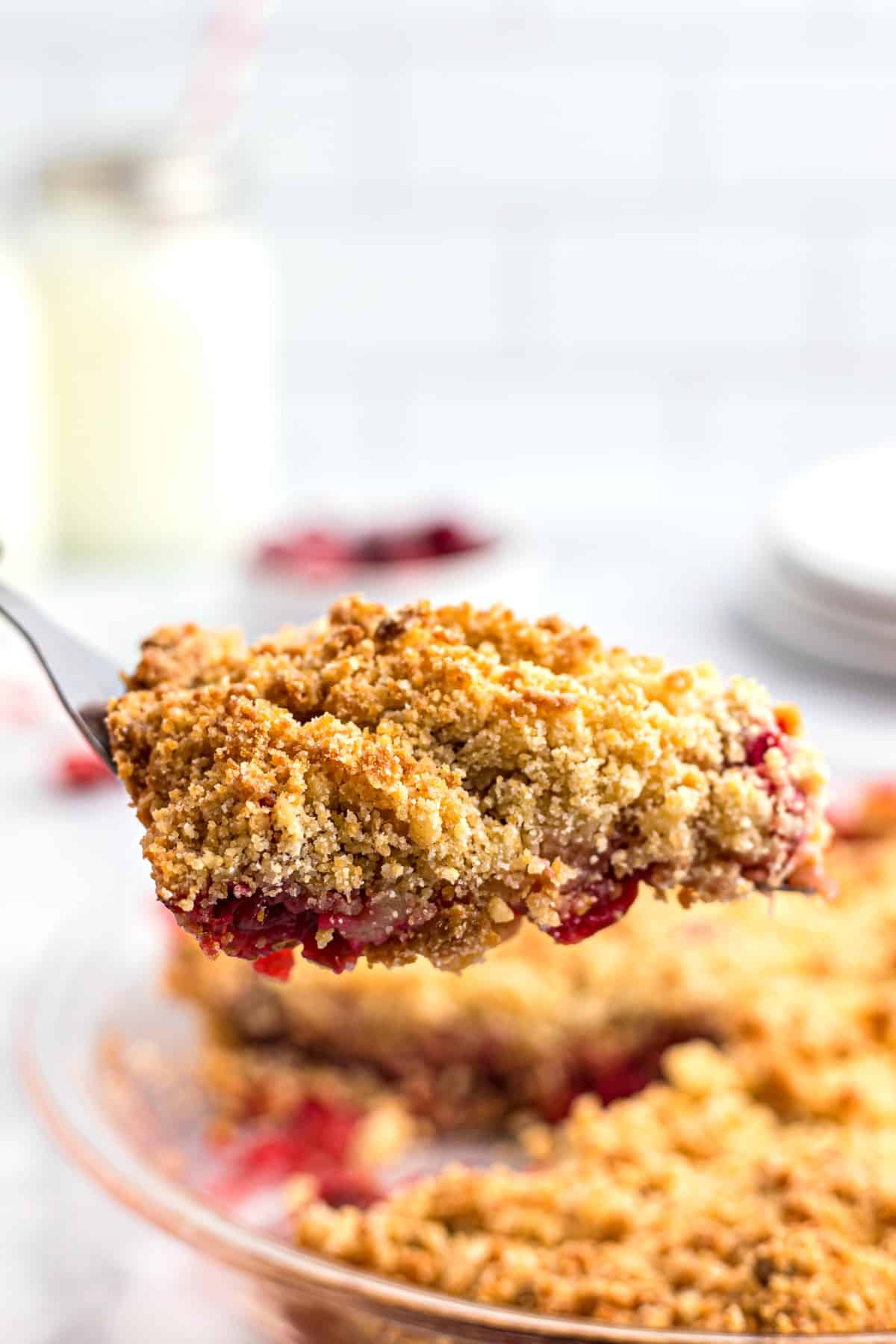 Slice of apple cranberry crumble being lifted out of the pie plate.