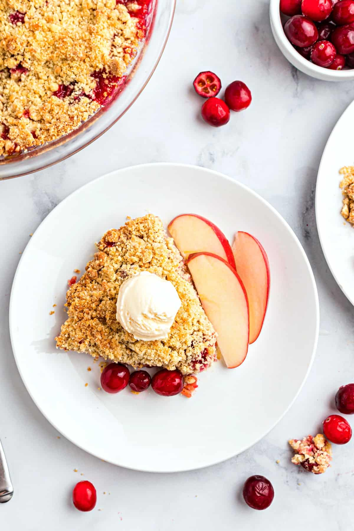 Apple cranberry crumble on a white plate served with vanilla ice cream and fresh apple slices.