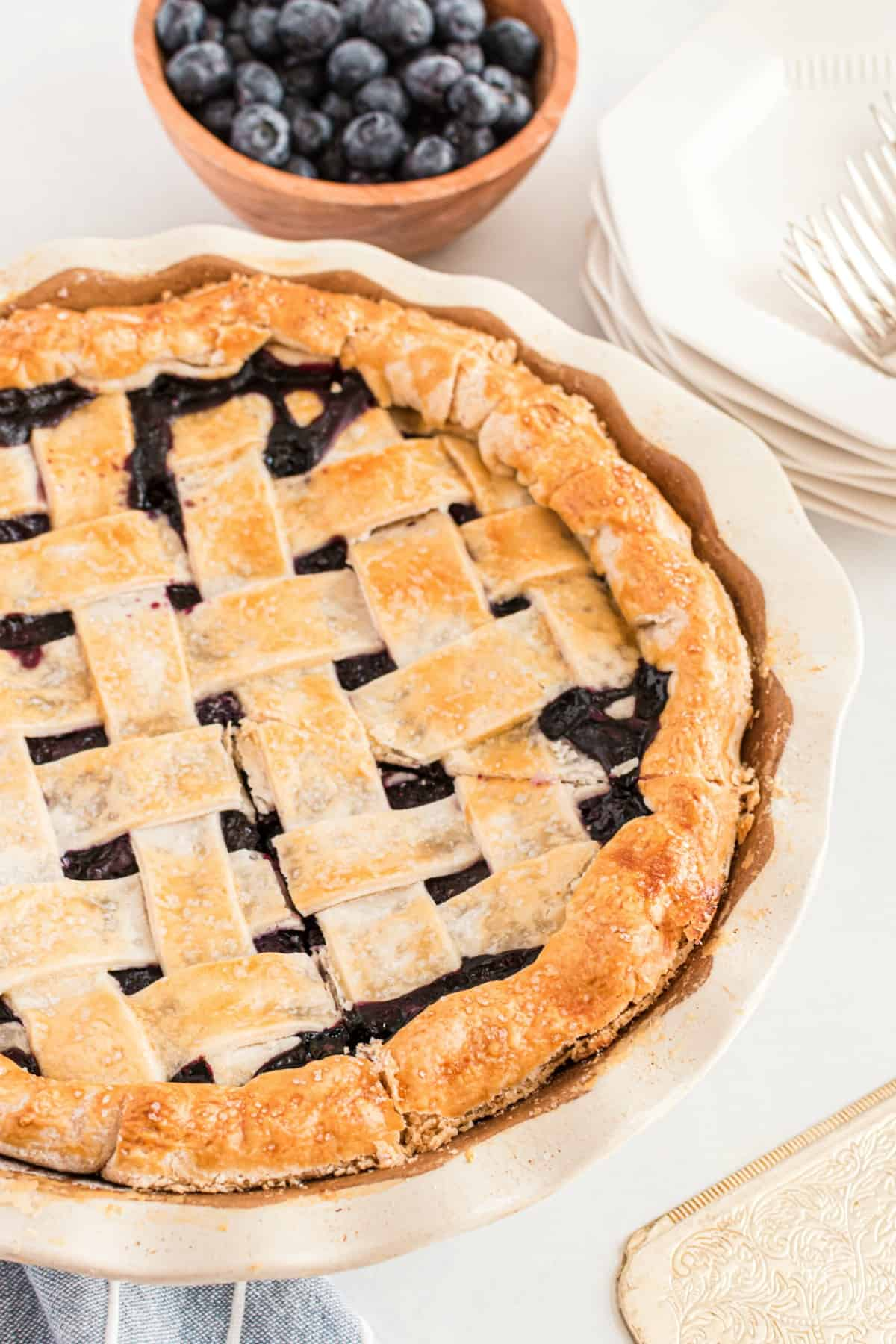 Blueberry pie with lattice crust in a white pie plate.