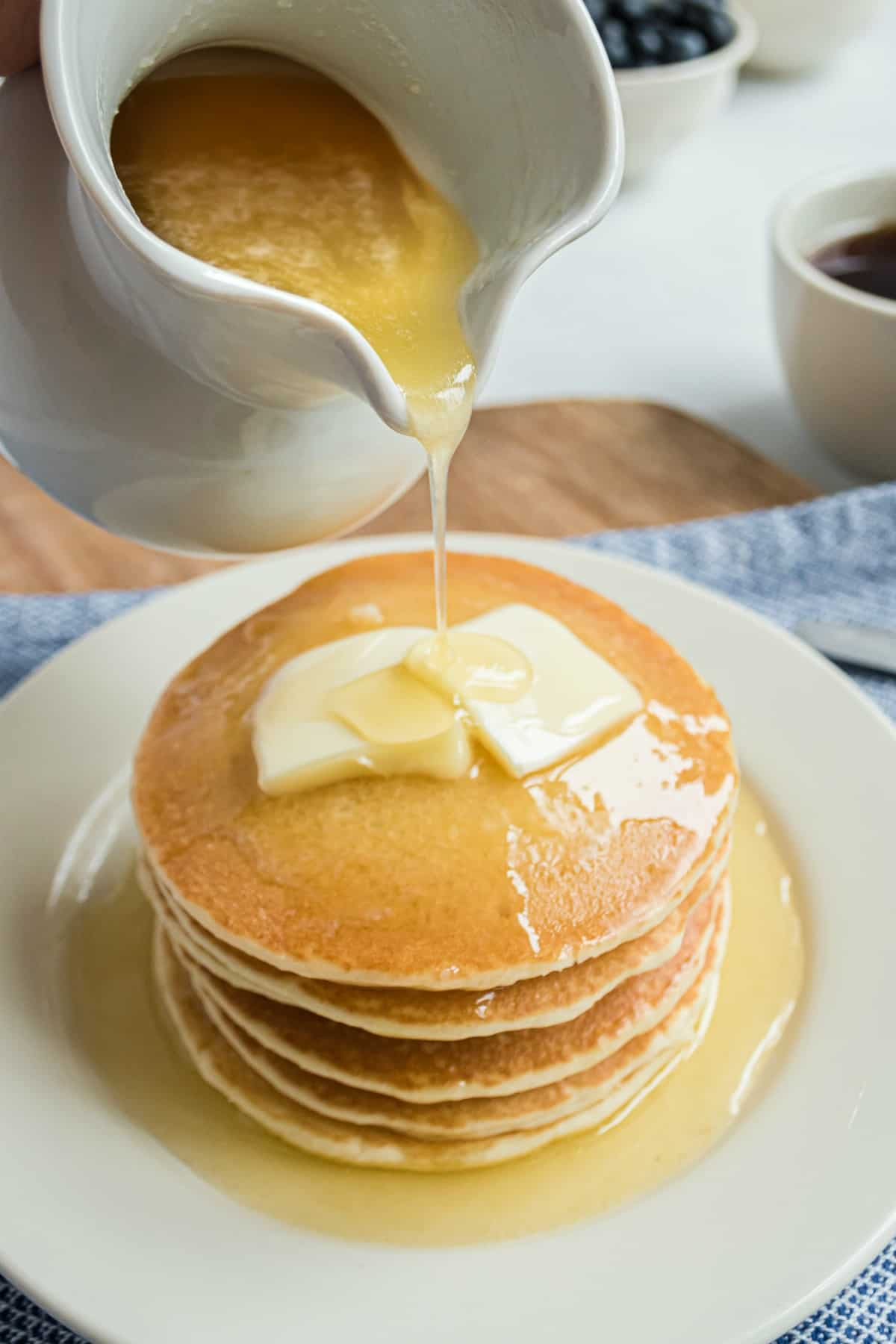 Buttermilk syrup in a white pitcher being poured over a stack of pancakes.