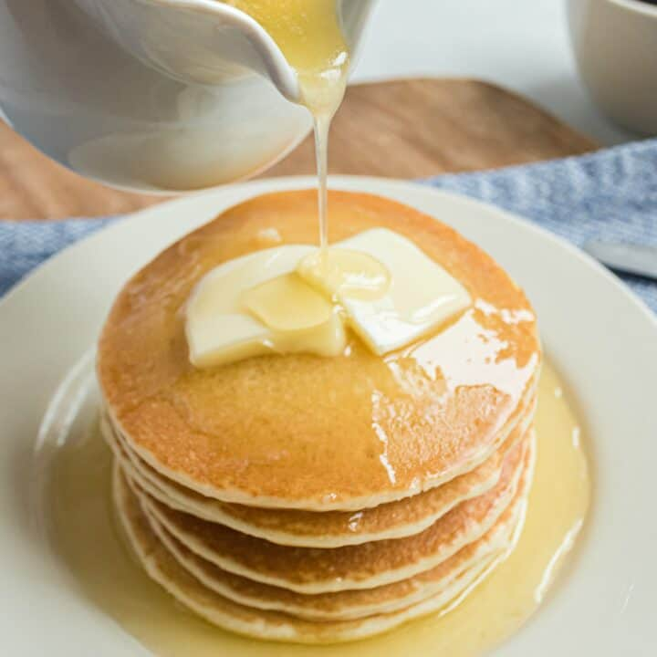 Stack of buttermilk pancakes being topped with a pour of buttermilk syrup.