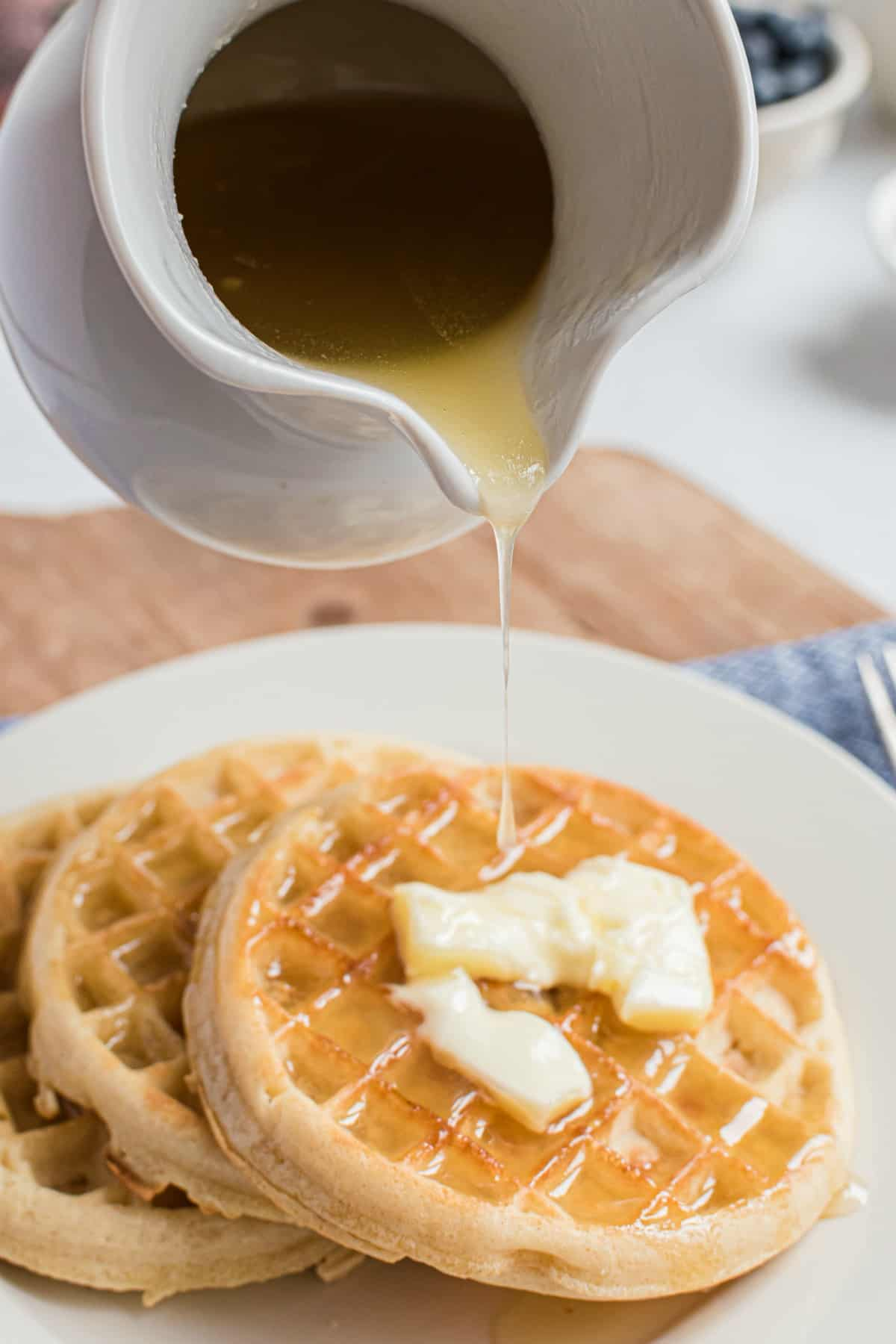 Homemade buttermilk syrup in a white pitcher being poured over a stack of homemade waffles.