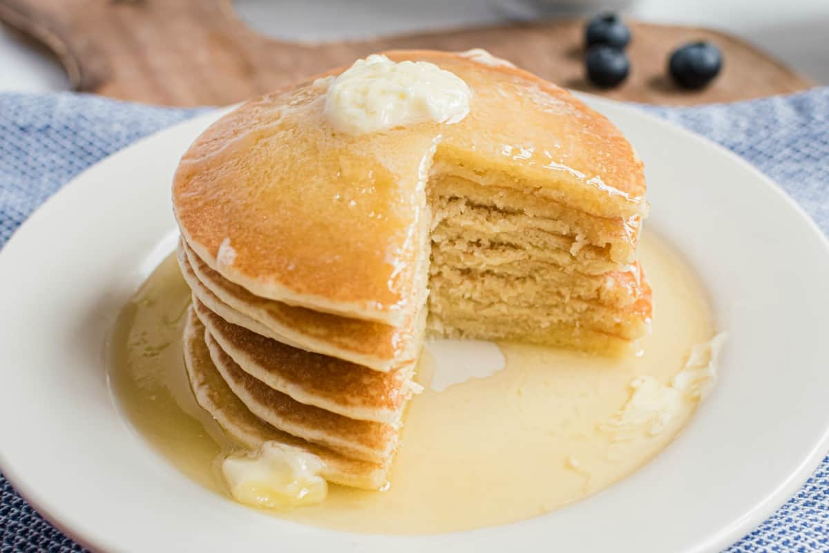 Stack of pancakes with a bite removed and covered in buttermilk syrup.