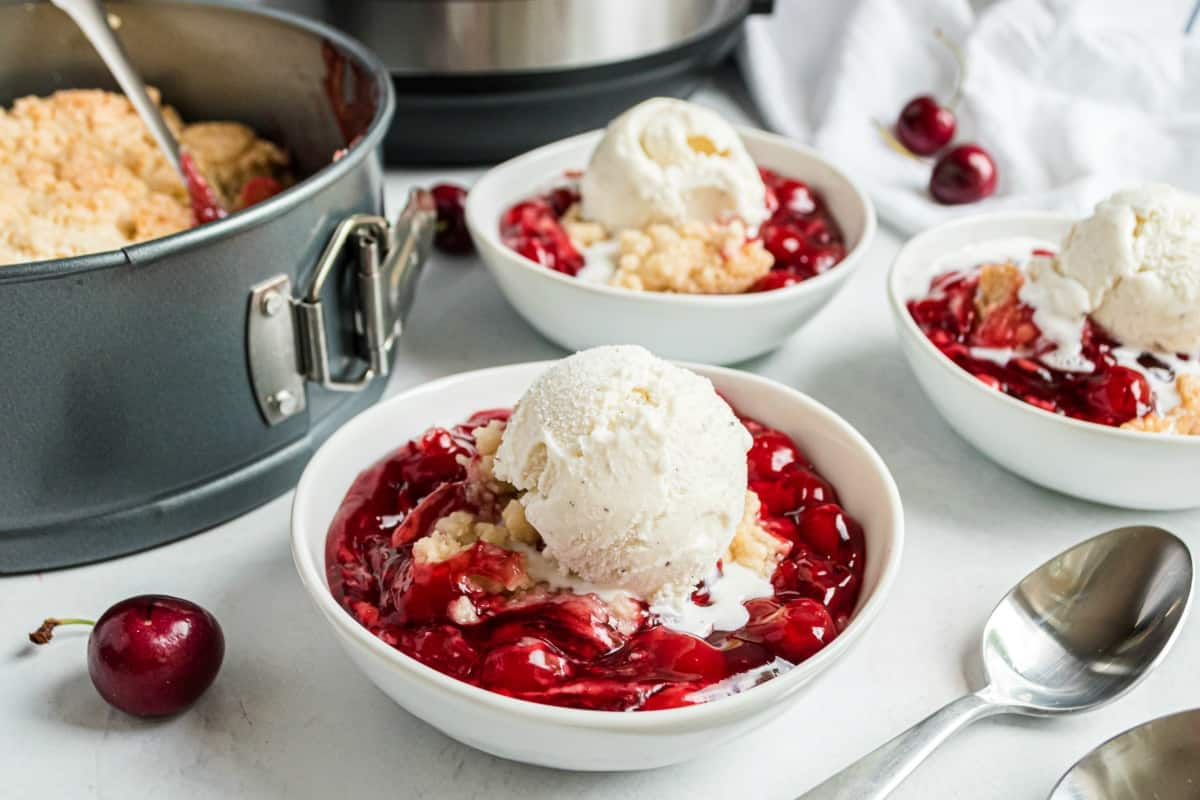 Cherry cobbler with vanilla ice cream in a bowl.