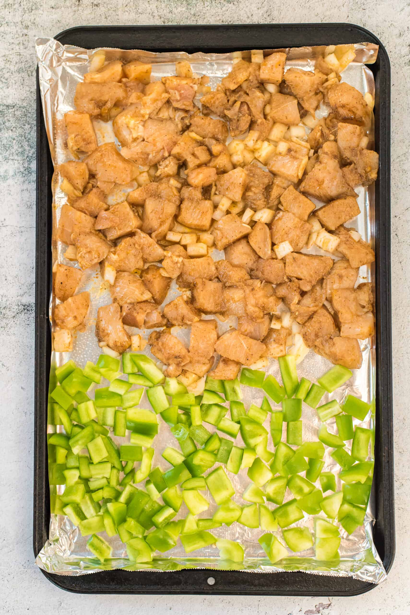 Baking sheet with chicken, onion, and peppers.