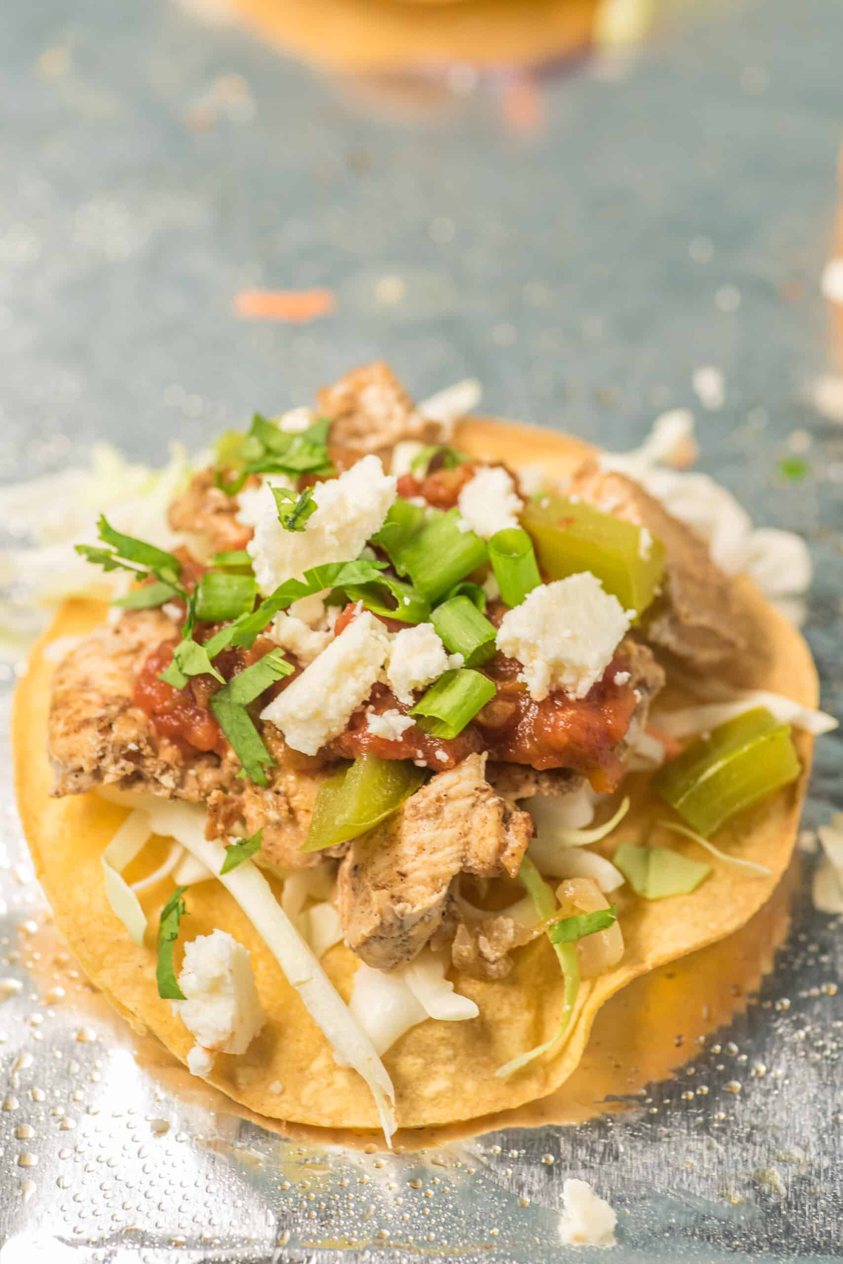 Chicken Tostada with all the fixings on a foil lined baking sheet.
