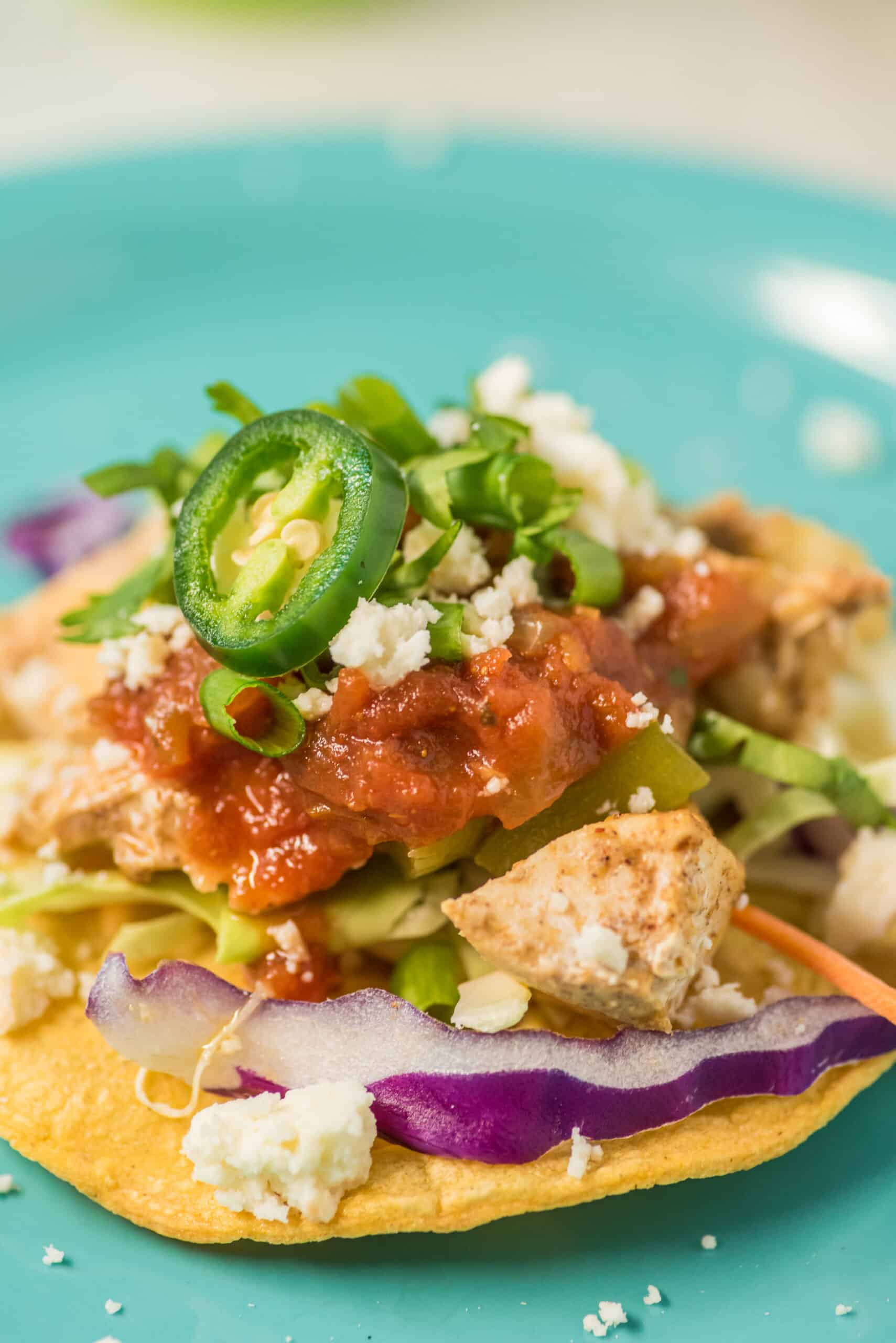 Tostada with chicken, salsa, cheese, jalapeno, and lettuce.