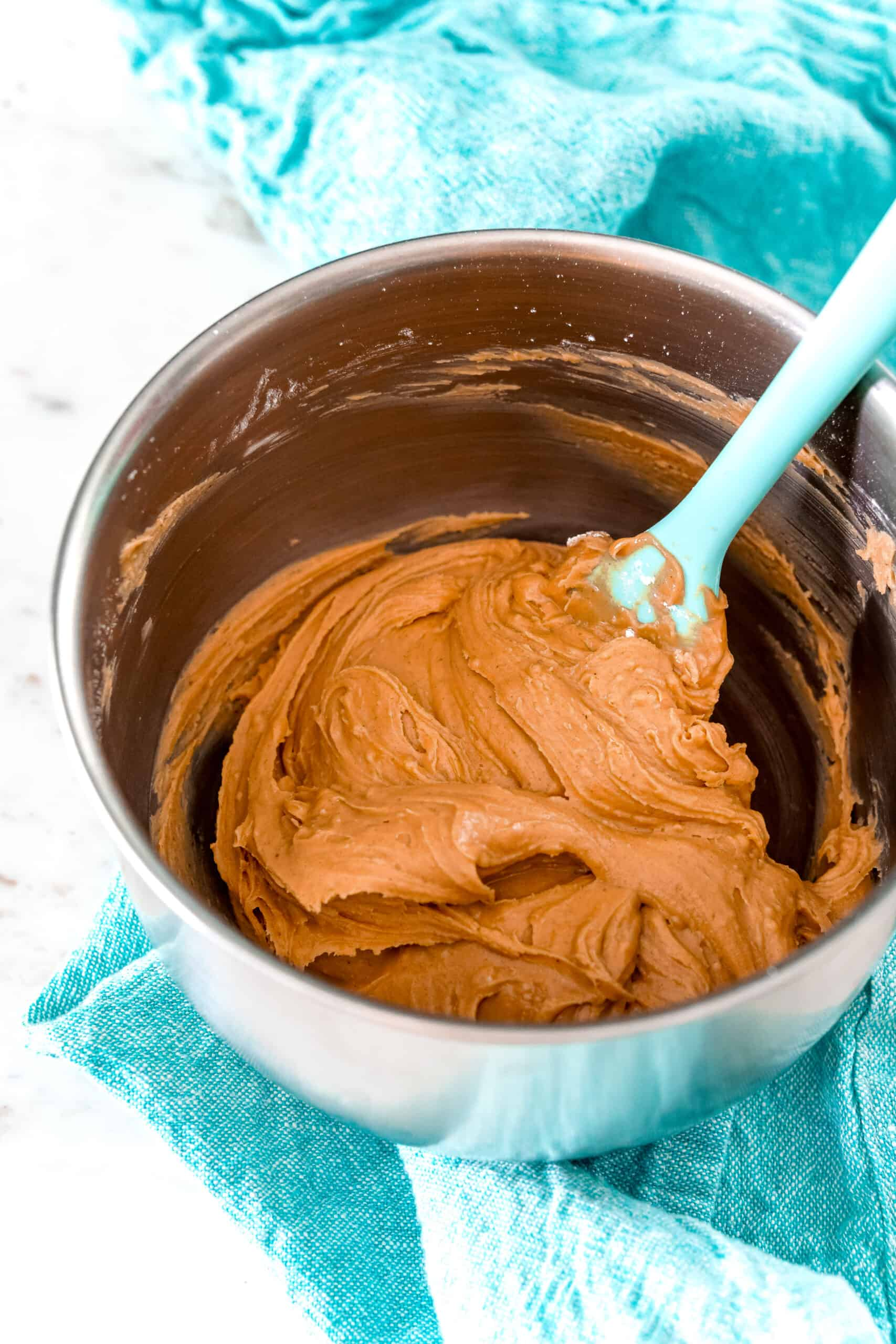 Peanut butter cup filling in a metal mixing bowl with teal napkin beneath the bowl.