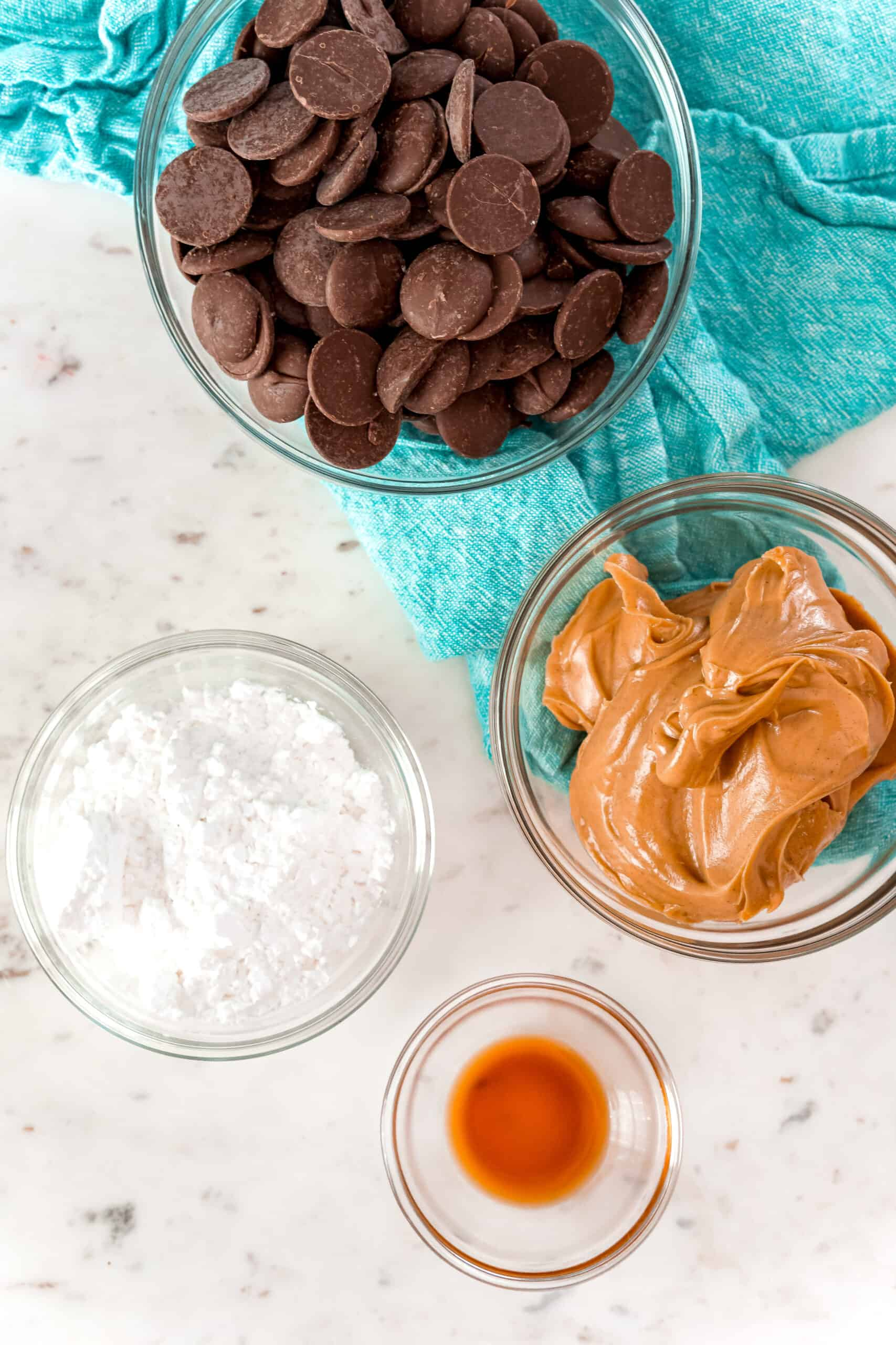 Four ingredients to make homemade peanut butter cups including chocolate, sugar, vanilla, and peanut butter.