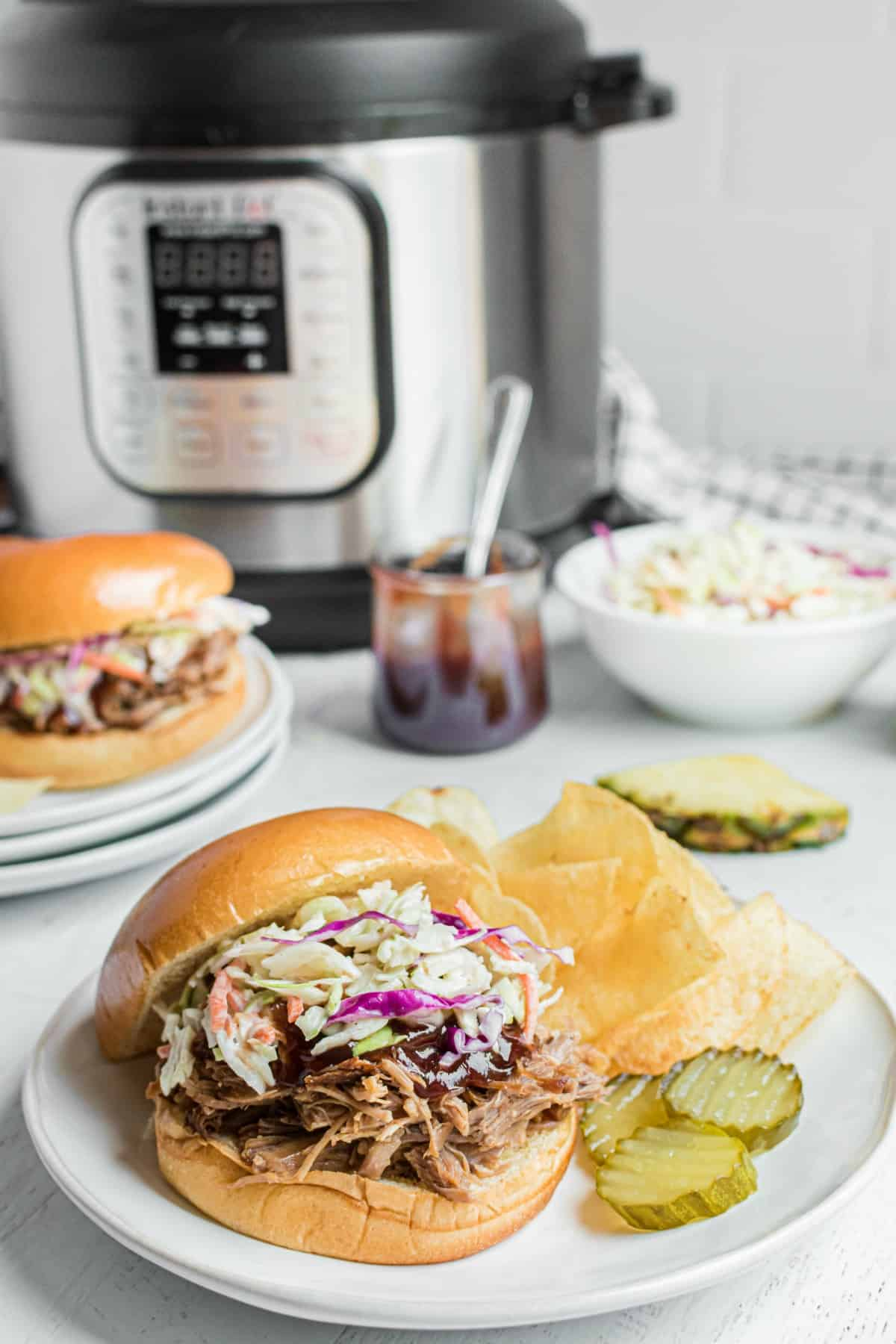 Hawaiian pork on a bun with bbq sauce and coleslaw with a side of chips and pickles. Instant pot in background.