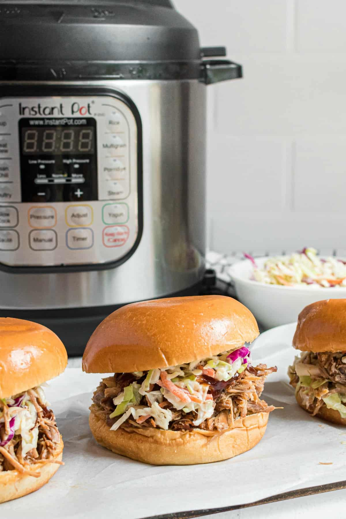 Instant Pot Hawaiian Pork sandwiches on a white plate with pressure cooker in background.