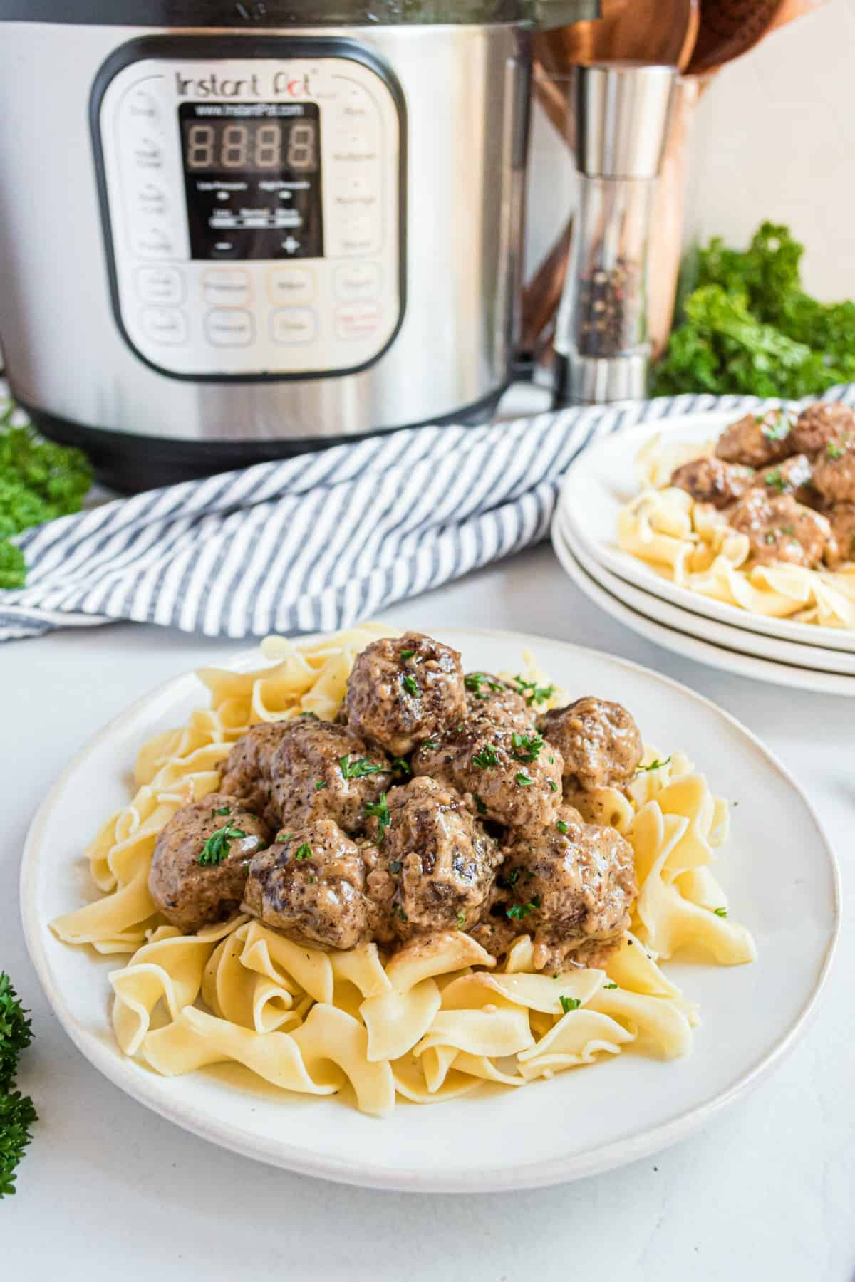 Swedish meatballs served on a plate of egg noodles with instant pot in background.