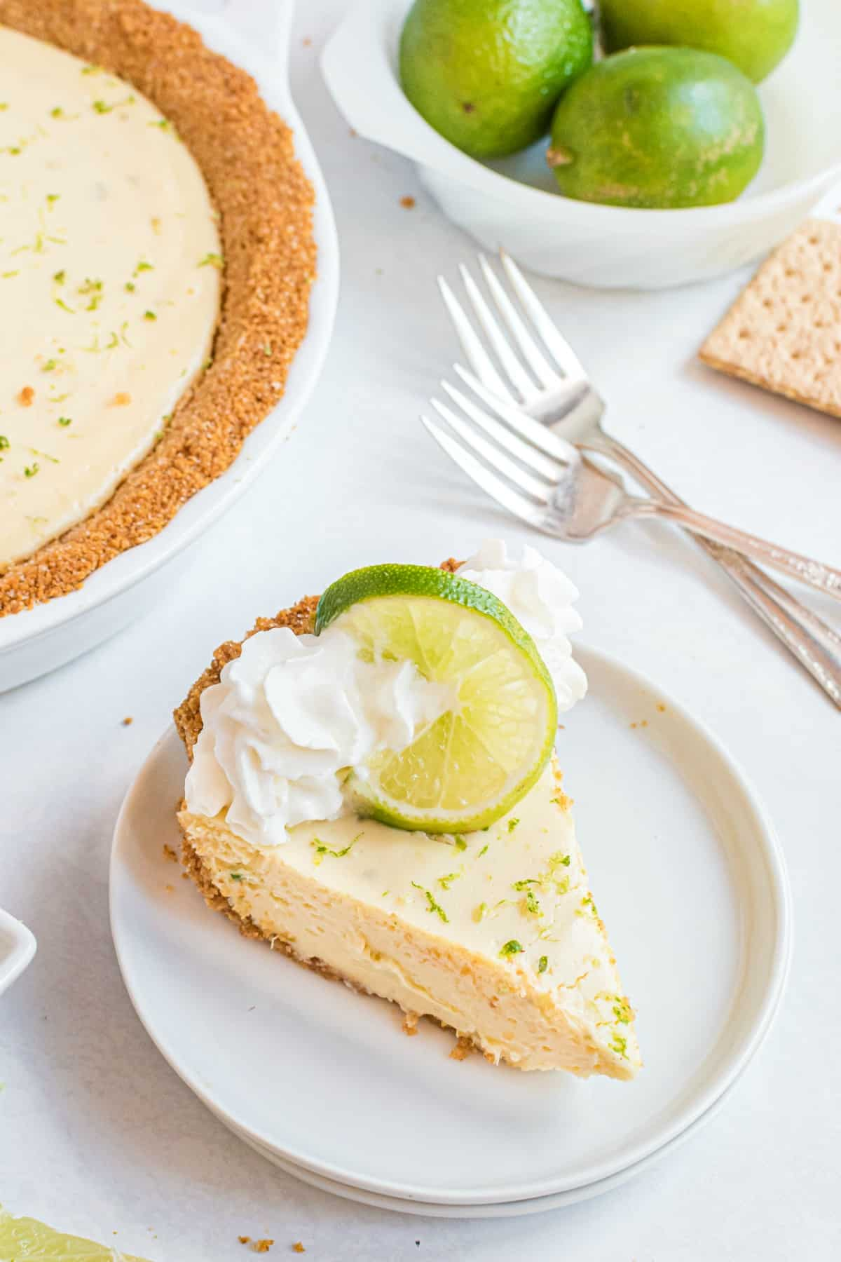 Slice of key lime pie on a white plate and garnished with whipped cream, lime zest, and a slice of lime.