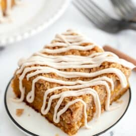 Pumpkin cake with cinnamon crumb and cream cheese frosting on a white dessert plate.