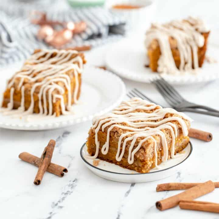 Pumpkin crumb cake with cream cheese frosting, sliced and served on three dessert plates.