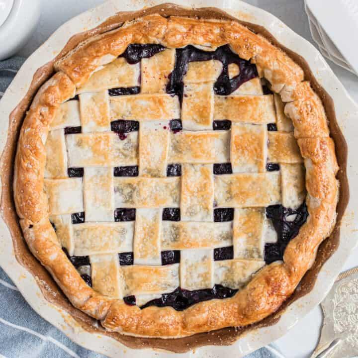 Blueberry pie with lattice pie crust in a deep dish pie plate.