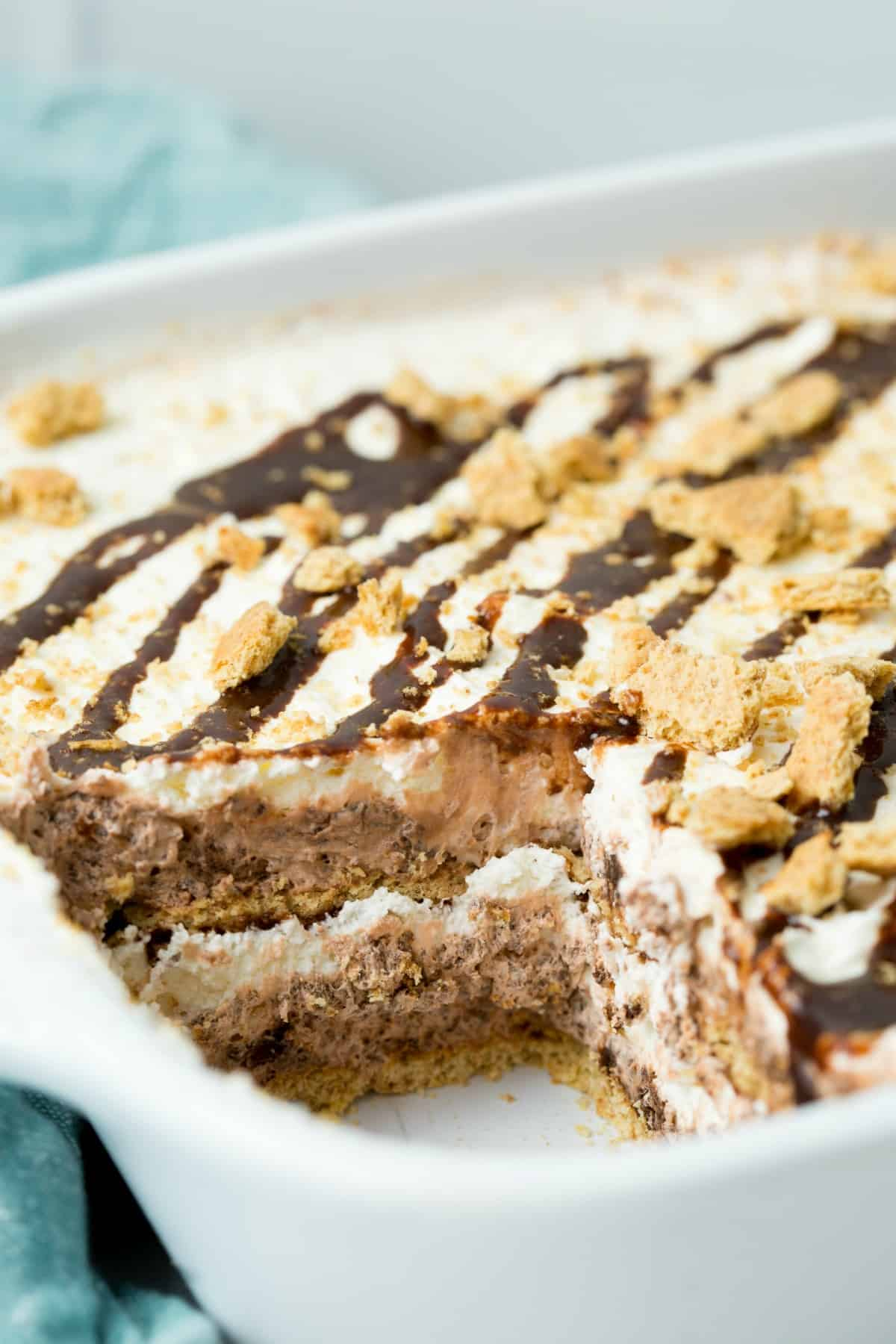 Slice removed from a white baking dish, and the layers of a smores icebox cake can be seen.