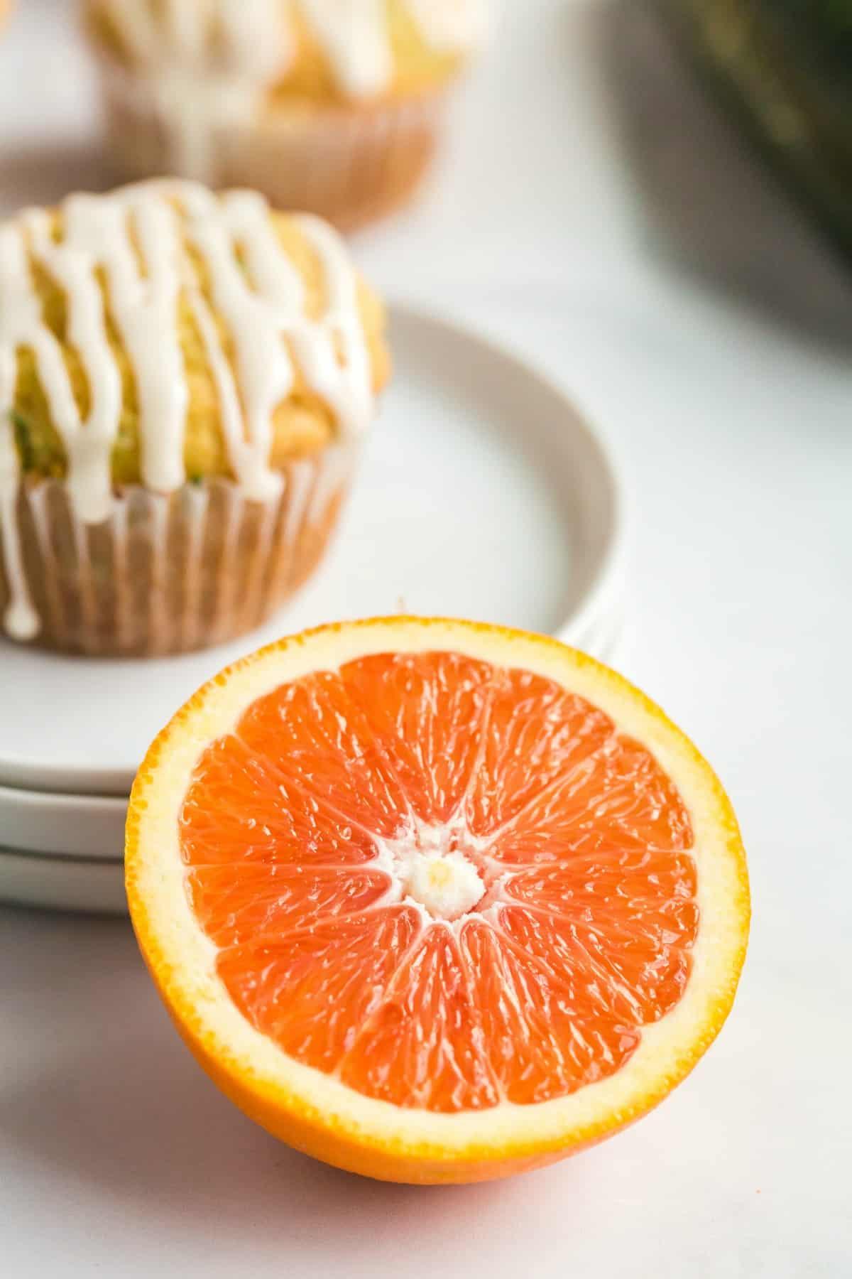 Cara cara orange sliced in half with zucchini muffin in background.