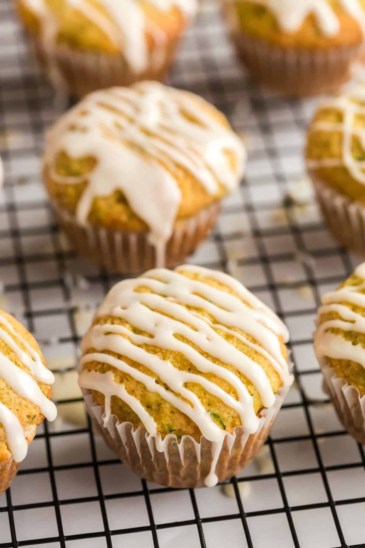 Zucchini muffins on a wire rack drizzled with orange glaze.