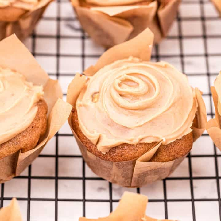 Apple muffins on wire rack topped with caramel icing.