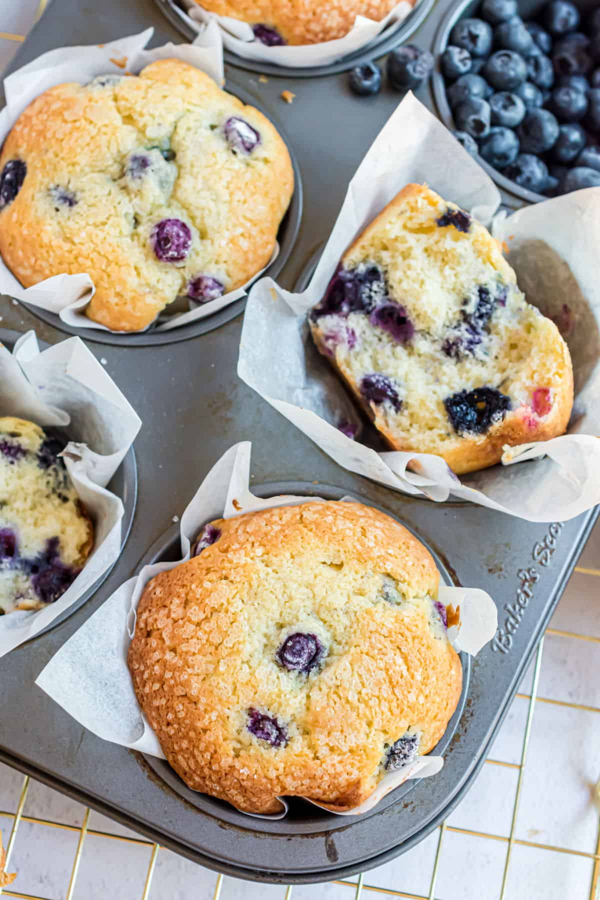 Blueberry muffins in muffin tin, some cut in half.