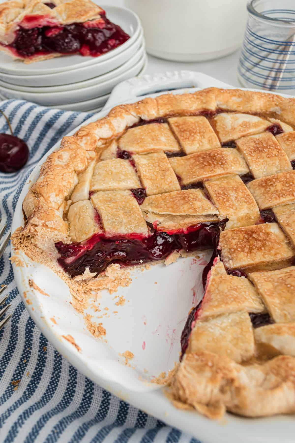 Whole cherry pie in a white pie plate with one slice removed.