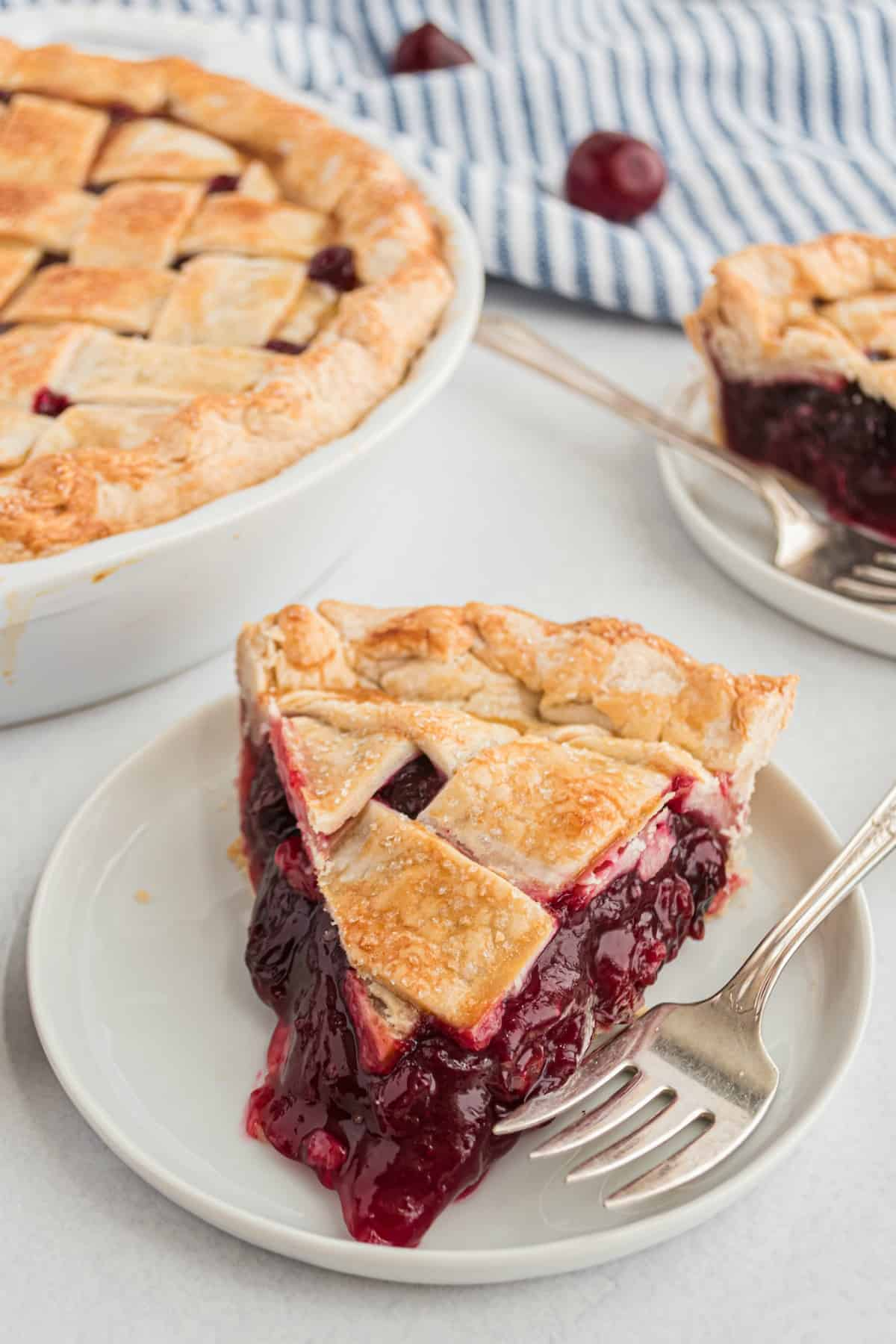 Slice of cherry pie with lattice crust on a white plate.