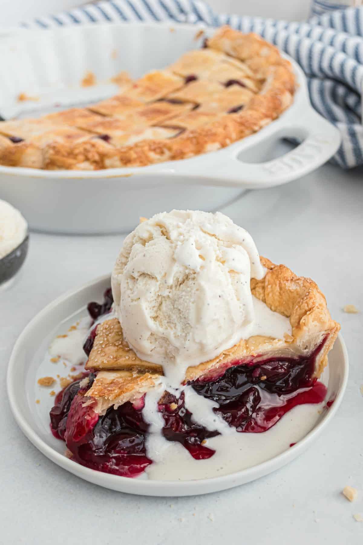 Slice of cherry pie with a scoop of vanilla ice cream melting on top.