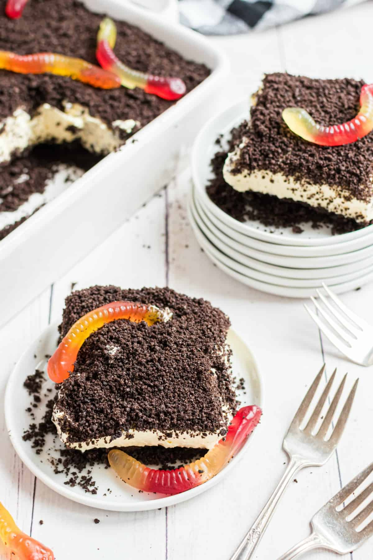 Vanilla dirt cake with gummi worms on top of crushed oreos.