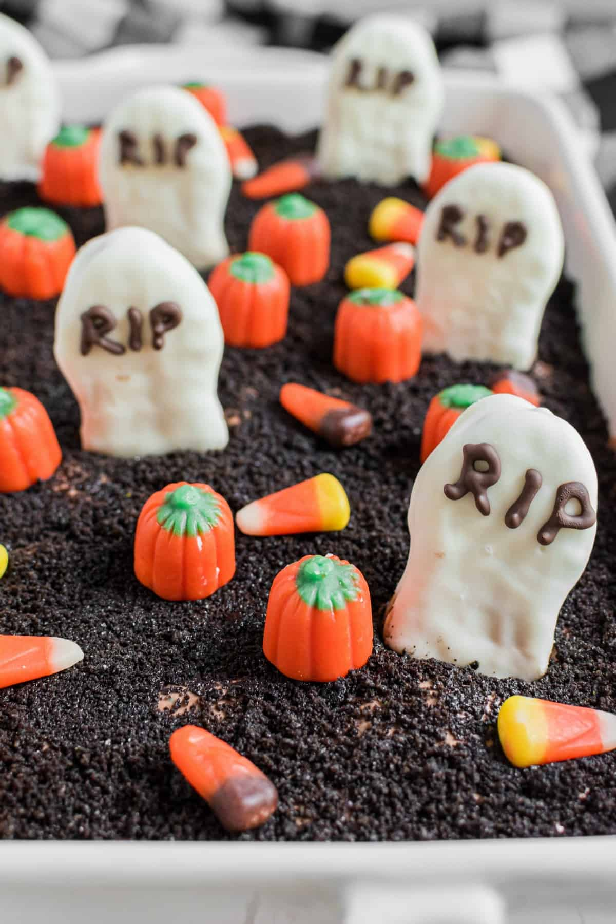 Close up of oreo topped dirt cake with tombstones and pumpkins.