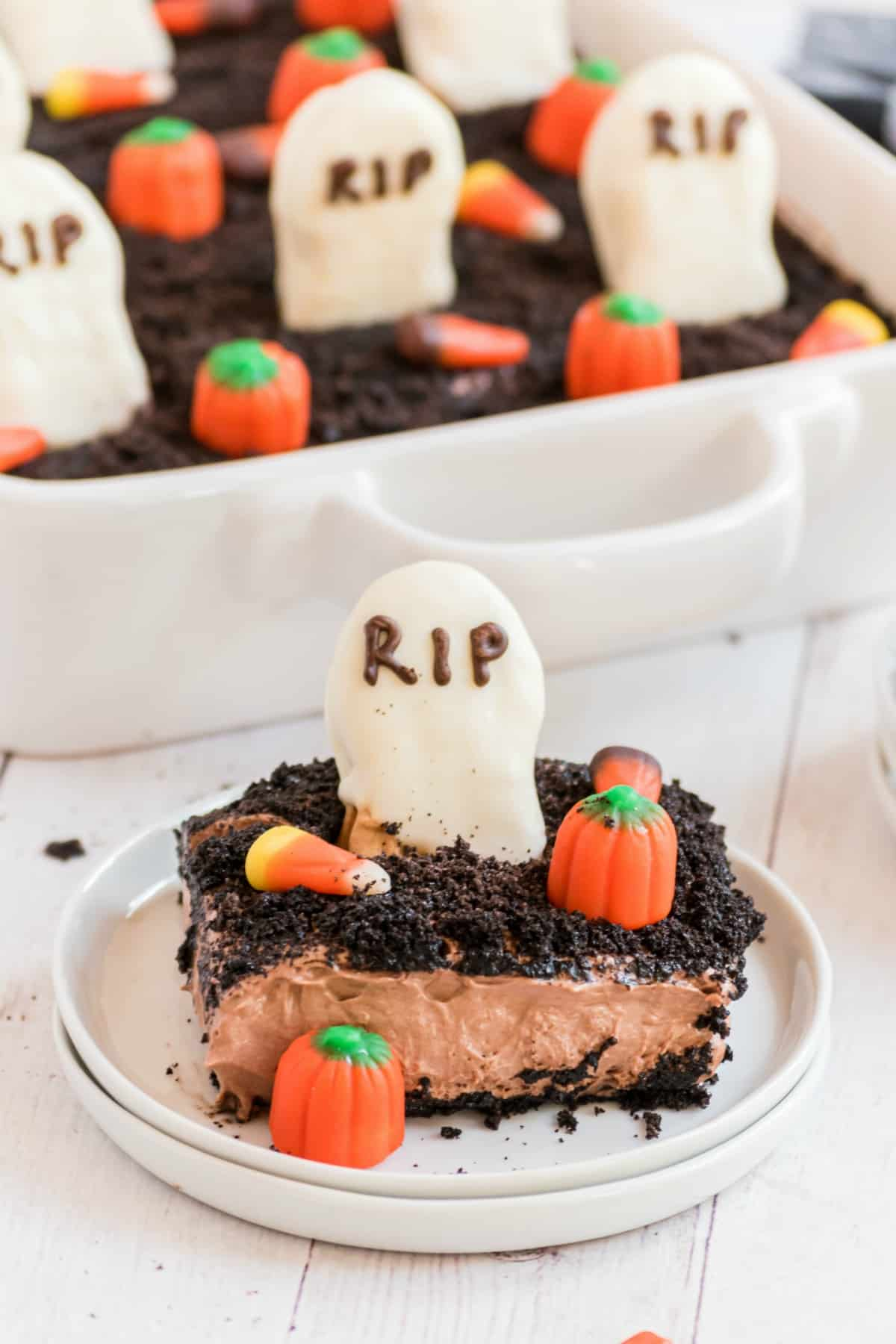Slice of dirt cake with oreos and topped with a graveyard theme.
