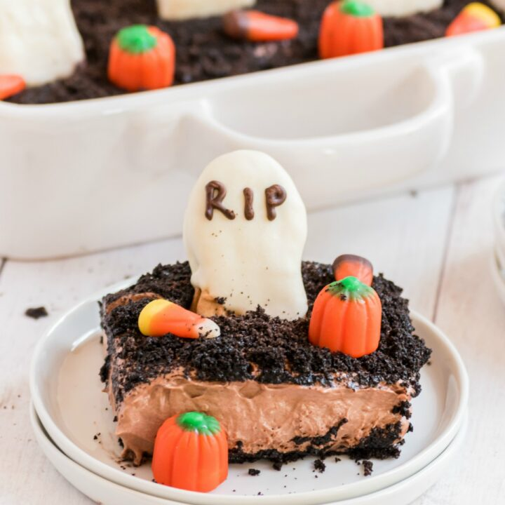 Slice of halloween dirt cake on a white plate, decorated with tombstone cookie and candy corn.