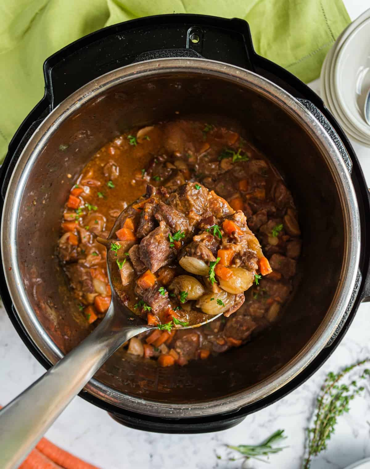 Beef bourguignon in the instant pot being lifted with a ladle.