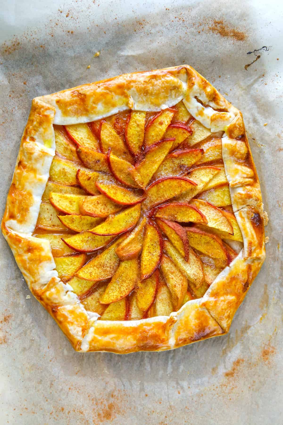 Rustic galette with peaches on parchment paper.