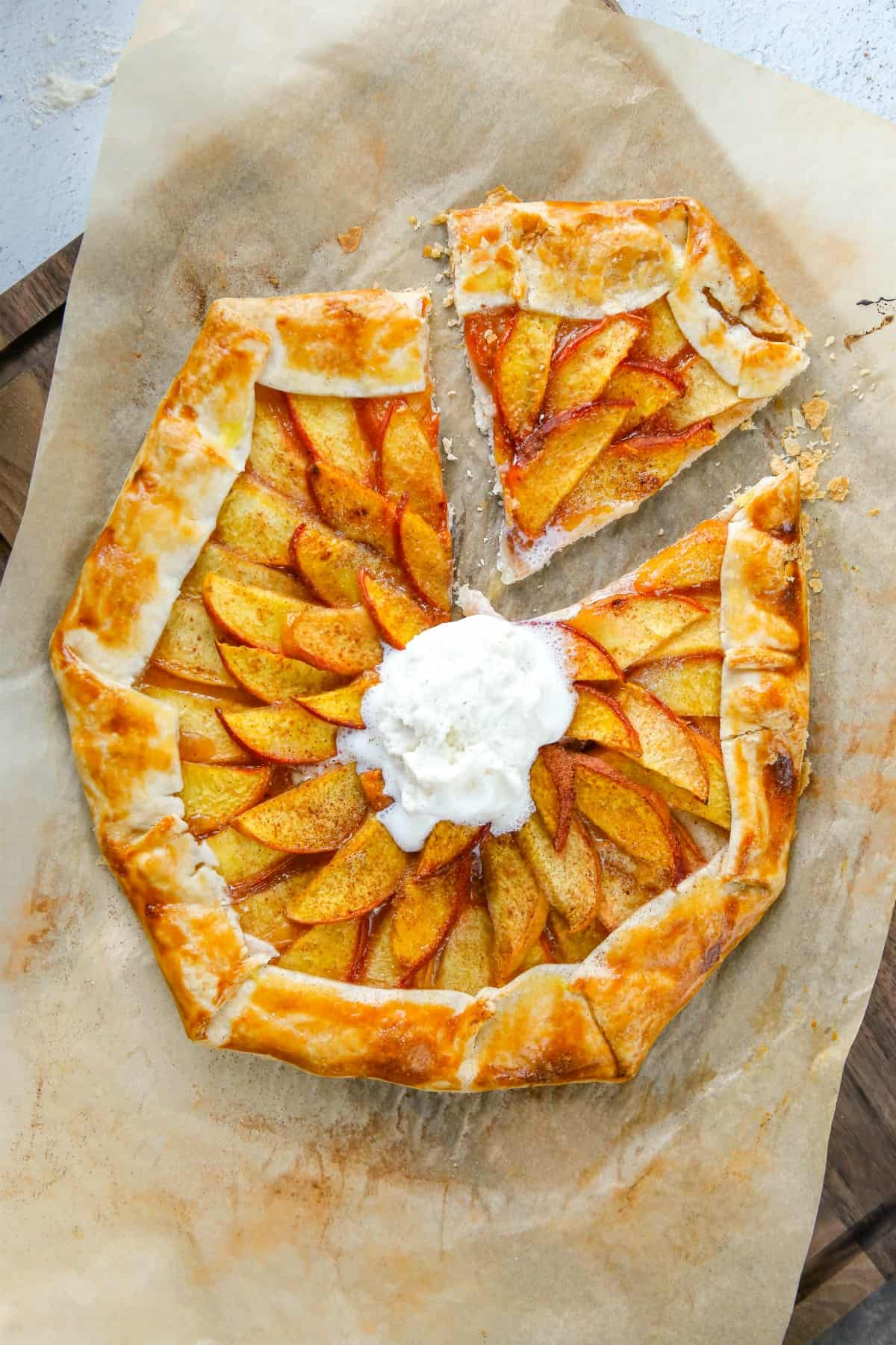 Peach galette with one slice cut and topped with ice cream.