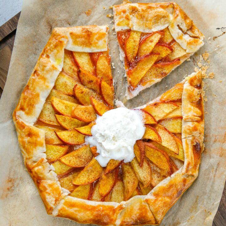 Peach galette with scoop of vanilla ice cream and one slice cut.