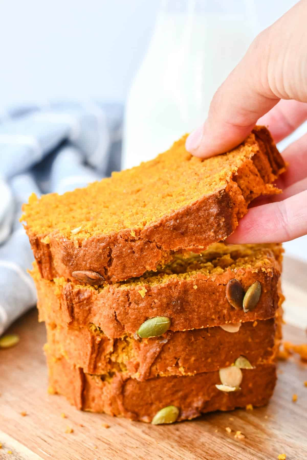 Stack of sliced pumpkin bread with one piece being lifted off stack.