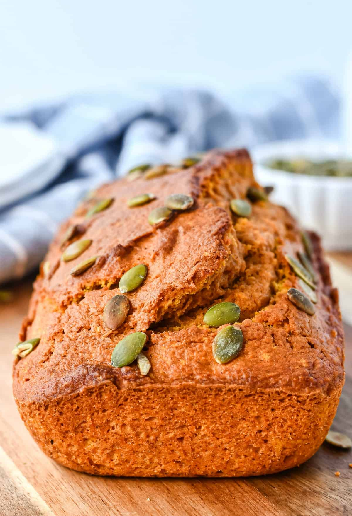 Loaf of pumpkin bread with pumpkin seeds on wooden cutting board.