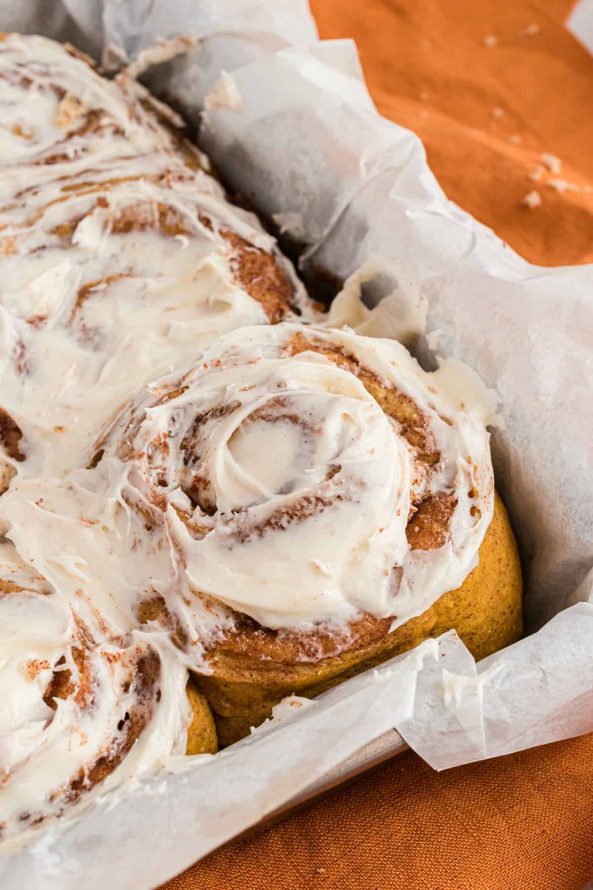 Pumpkin cinnamon rolls in parchment paper lined baking dish with maple icing.